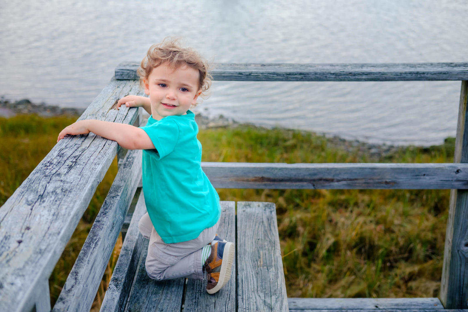 Portrait of a toddler boy with curly windswept hair in a green shirt kneeling on a wooden dock