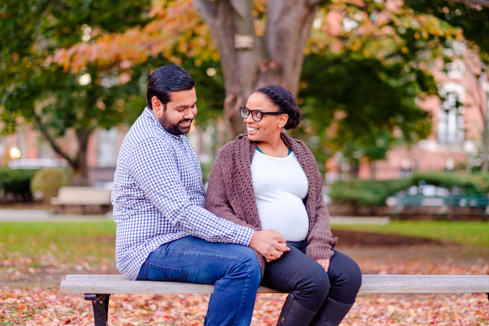 Maternity portraits with couple sitting on a bench holding hands in a fall park setting
